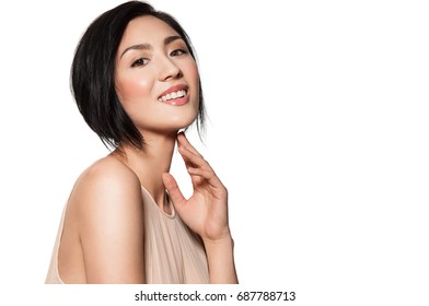 Smiling beautiful Korean woman with natural make-up in evening dress in pink color, isolated on white background