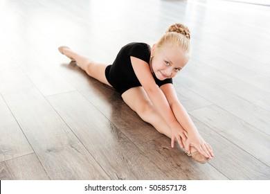 Smiling beautiful little girl ballerina doing twine in ballet studio