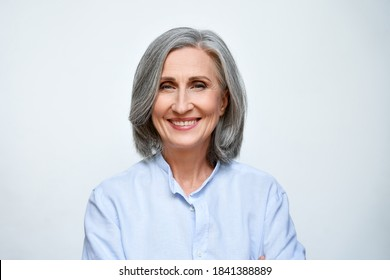 Smiling beautiful mature business woman standing isolated on white background. Older senior businesswoman, 60s grey haired lady professional coach looking at camera, close up face headshot portrait.