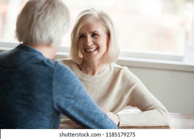 Smiling beautiful mature woman listening to elderly man talking, senior happy retired family enjoying pleasant conversation, senior couple dating concept, good relations love in older people marriage