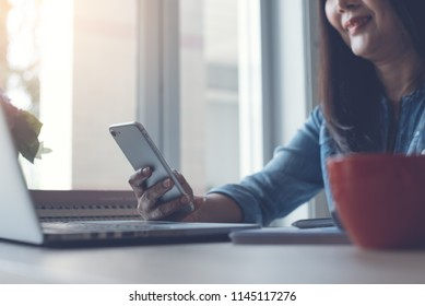 Smiling beautiful middle age asian business woman, freelancer relaxed using mobile smart phone, video calling, working on laptop computer with cup of coffee on office desk, cropped image