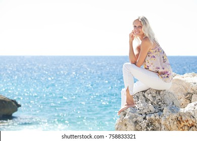 Smiling beautiful middle age woman sitting relaxing on cliff contemplating the sea on sunny holiday destination, looking at camera outdoors. Healthy wellness travel recreation lifestyle in nature.
