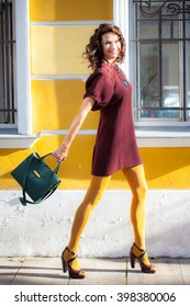 Smiling beautiful middle-aged woman walking down the street and waving a new green hand-bag