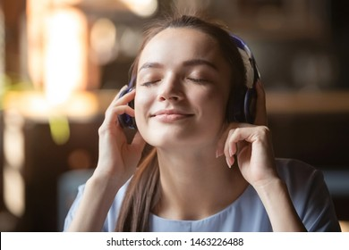 Smiling beautiful millennial girl wearing modern Bluetooth earphones enjoy music playing, happy young woman in headphones listen to favorite tracks like quality sound beats. New technology concept