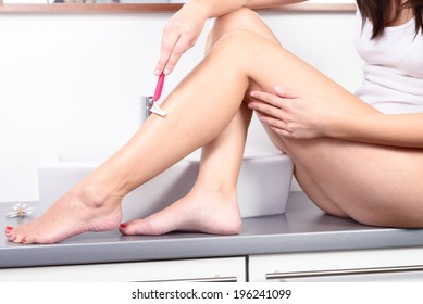 Smiling beautiful naked young woman shaving the hair on her legs with a pink disposable razor sitting on the vanity, spa and beauty concept