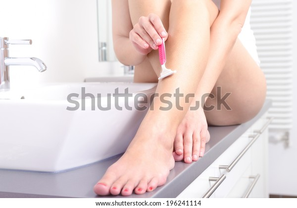 Smiling beautiful naked young woman shaving the hair on her legs with a pink disposable razor in the bath in a personal hygiene, spa and beauty concept