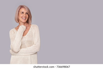 smiling beautiful old woman looking up to copy space. Isolated on grey