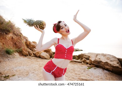 44ac382bc27a6 Smiling beautiful pinup girl in headband posing with pineapple at the beach
