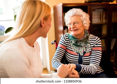 Smiling beautiful senior happy woman with her daughter enjoy talking at home