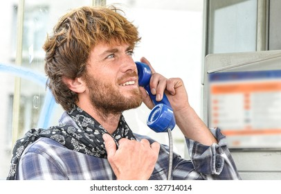 smiling beautiful senior man speaking in old phone in french phone box