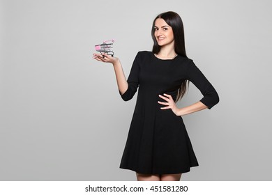 Smiling beautiful woman in black dress holding small empty shopping cart blank copy space over gray background