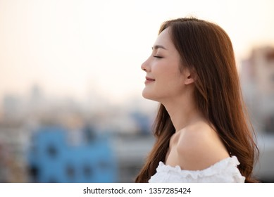 Smiling Beautiful Woman breathing fresh air at outdoor. Closed eyes.