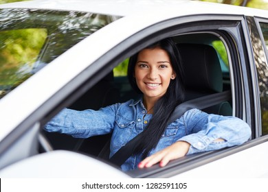 Smiling beautiful woman driving her car