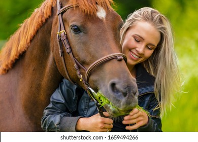 Smiling beautiful woman feeding her arabian horse with grass in the field