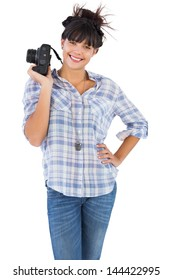 Smiling beautiful woman with her hand on hip and holding camera on white background