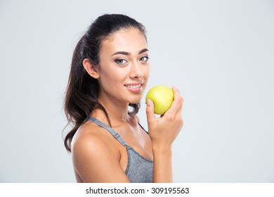 Smiling beautiful woman holding apple isolated on a white background. Looking at camera