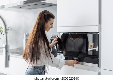 Smiling beautiful woman housewife preparing food in electric microwave oven, adjusting temperature on it. Happy female using modern kitchen built-in appliance