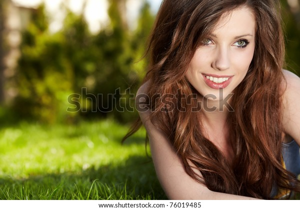 Smiling beautiful woman laying on grass