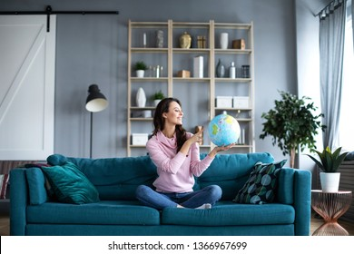 Smiling beautiful woman is looking at a model of the globe sitting on a sofa. Choose a place to travel.