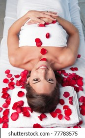 Smiling beautiful woman lying on a massage table with rose petals around