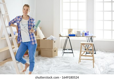 Hermosa mujer sonriente pintando paredes interiores de casa