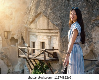 Smiling beautiful woman portrait in front of Cappadocia landscape at sunset. Turkey.
