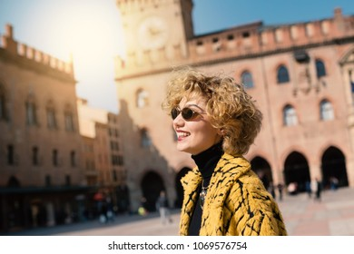 Smiling beautiful woman portrait outdoors in Piazza Maggiore, Bologna, Italy. Natual flare.