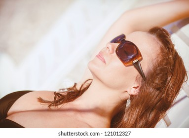 Smiling beautiful woman sunbathing on a beach