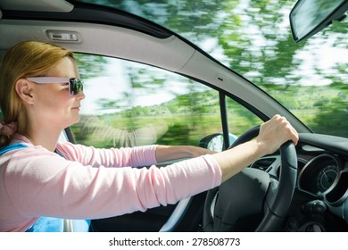 Smiling beautiful woman in sunglasses driving at high speed car with panoramic windshield. Internal stock photo with low shutter speed and blurred in motion natural background.