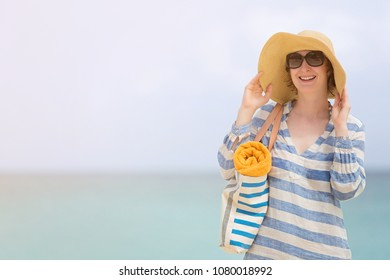 smiling beautiful woman in sunglasses and sunhat enjoying summer beach vacation, copy space on left