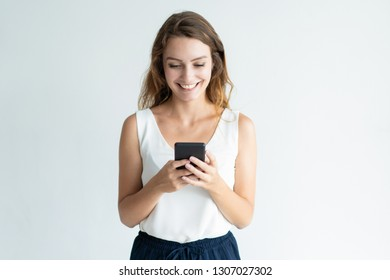 Smiling beautiful woman texting on smartphone. Lady standing and using digital gadget. Communication concept. Isolated front view on white background.