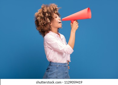 Smiling beautiful young African American woman with curly afro hair screaming by megaphone.