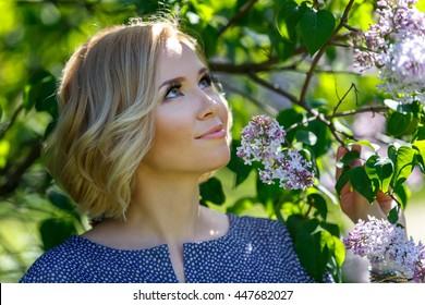 Smiling beautiful young blond girl near lilac bush