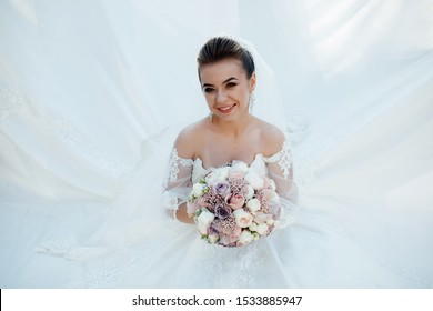 Smiling beautiful young bride. Fashion, beauty, style. Beauty portrait of bride. Beautiful bride with make up and hairstyle. Young attractive bride with bouquet of flowers.