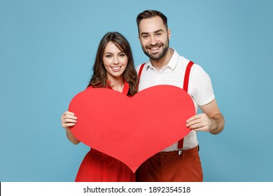 Smiling beautiful young couple two friends man woman wearing white red clothes standing hold big heart isolated on pastel blue color background studio portrait. St. Valentine's Day holiday concept