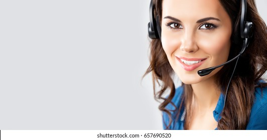 Smiling beautiful young female support phone operator in headset, over grey background, with blank copyspace area for advertising slogan or text message. Help servise and client consulting concept.