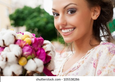 smiling beautiful young girl with bouquet of flowers. Outdoors