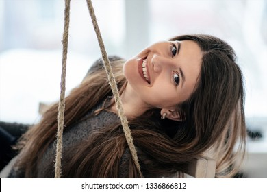 Smiling beautiful young girl with diastema sitting on swing bench in studio. She looks at the camera. She tilted her head aside