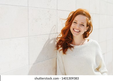Smiling beautiful young red-haired woman in knitted sweater standing outdoor in sunny day, leaning on white tiled wall and looking at camera. Front portrait with copy space