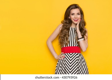 Smiling beautiful young woman in black and white striped dress posing with hand on chin and looking away. Three quarter length studio shot on yellow background.