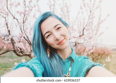 Smiling beautiful young woman with blue hair taking selfie in blossoming spring garden.