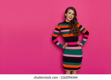 2f1cf0b8dcd Smiling beautiful young woman in colorful vibrant striped dress is posing  with hands on hip and