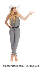 Smiling beautiful young woman in dotted jumpsuit, white sun hat and high heels is standing with legs crossed, looking away and pointing with pistol hand sign. Full length studio shot isolated