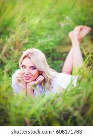 Smiling beautiful young woman lying among the green grass