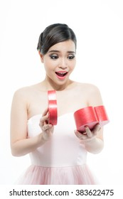 Smiling beautiful young woman opening a heart gift box. Isolated on white background.