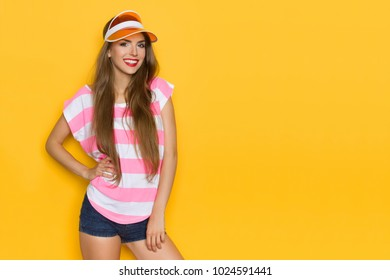 Smiling beautiful young woman in pink striped shirt, orange sun hat and jeans shorts is looking at camera. Three quarter length studio shot on yellow background.