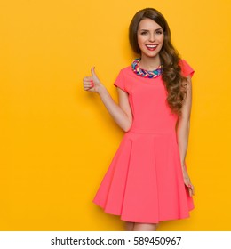 Smiling beautiful young woman in pink mini dress with colorful braided necklace showing thumb up. Three quarter length studio shot on yellow background.