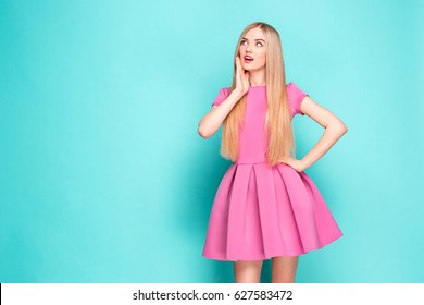 93bb77d1616e6 Smiling beautiful young woman in pink mini dress posing, presenting  something and looking away.