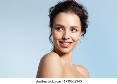 Smiling beautiful young woman with pure face skin looking over naked shoulder stand sideway headshot studio portrait. Happy, glad girl in playful, joyful mood satisfied with excellent skin