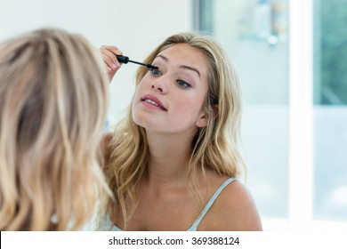 Smiling beautiful young woman putting on mascara in the bathroom mirror at home